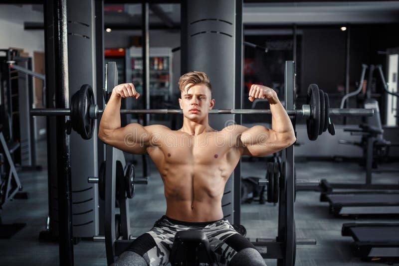 Ciérrese para arriba de pesos de elevación musculares de un hombre joven en gimnasio en fondo oscuro foto de archivo libre de regalías