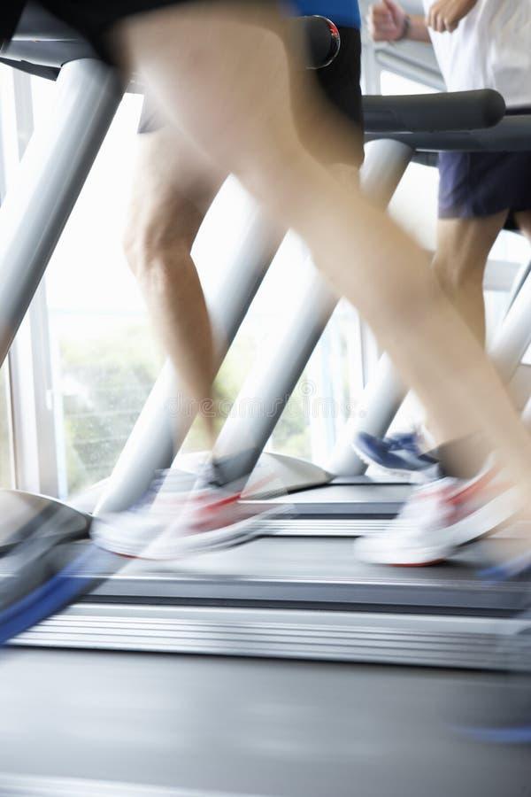 Ciérrese para arriba de 3 pies de los corredores en la máquina corriente en gimnasio foto de archivo libre de regalías