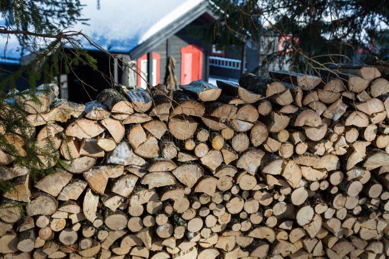 Ciérrese para arriba de pila de madera recientemente tajada con una cabina en el backgr imágenes de archivo libres de regalías