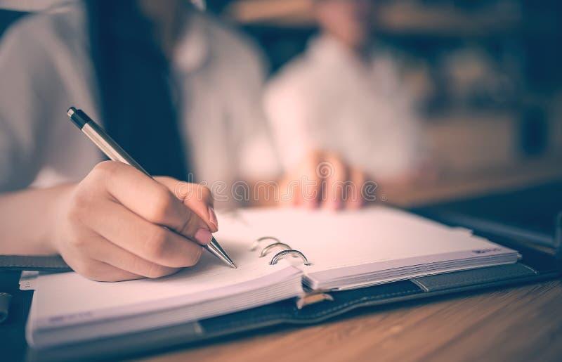Ciérrese para arriba de pluma y de la escritura de tenencia de la mano de la mujer en el cuaderno foto de archivo