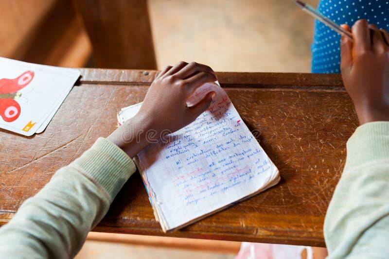 Ciérrese para arriba de poca mano del niño africano en la escuela con la escritura de la pluma y del aprendizaje en el escritorio foto de archivo libre de regalías