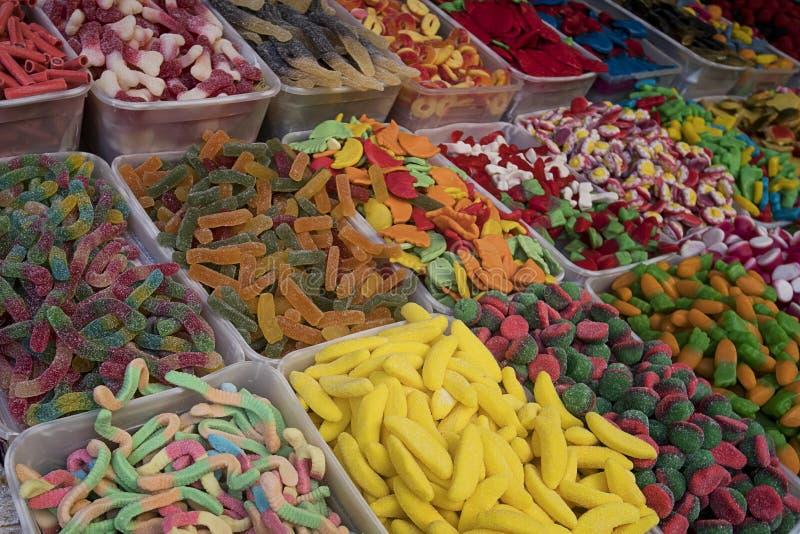 Ciérrese para arriba de poner en contraste los caramelos coloridos en cajas plásticas en la calle Venta de la confitería y de los foto de archivo libre de regalías