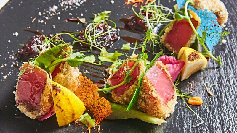 Ciérrese para arriba de rebanadas chamuscadas raras del atún de Ahi con la ensalada de las verduras frescas en una placa foto de archivo libre de regalías