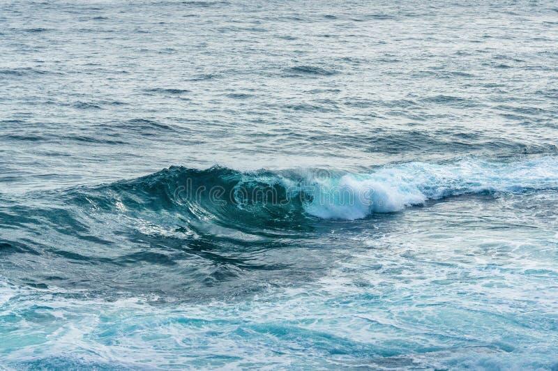 Ciérrese para arriba de remolino grande de la ola oceánica con la espuma blanca imágenes de archivo libres de regalías