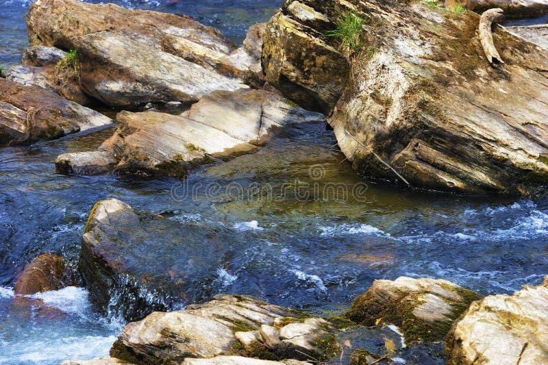 Ciérrese para arriba de rocas en un río que fluye foto de archivo libre de regalías