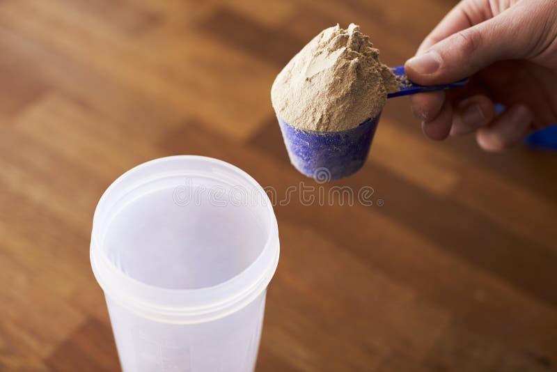 Ciérrese para arriba de sacudida de mezcla de la proteína del hombre en taza imagenes de archivo
