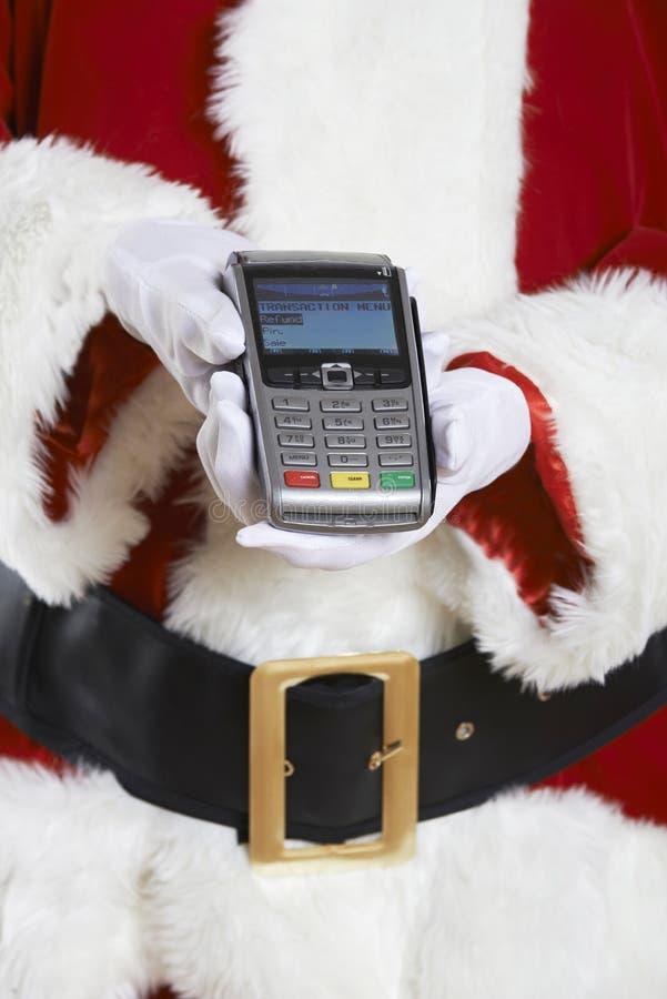 Ciérrese para arriba de Santa Claus Holding Credit Card Reader imagen de archivo