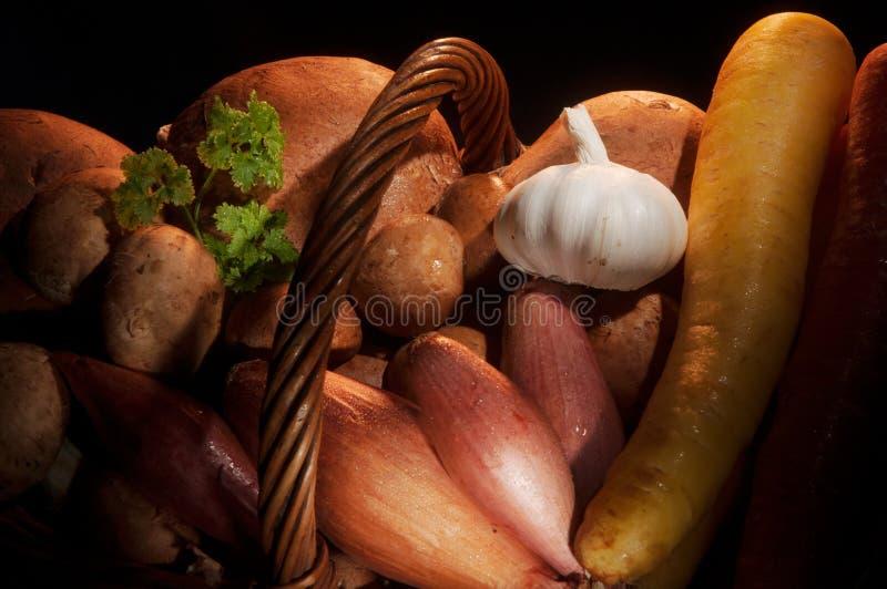 Ciérrese para arriba de setas y de verduras de raíz con las especias bajo iluminación caliente en una cesta de mimbre imagenes de archivo