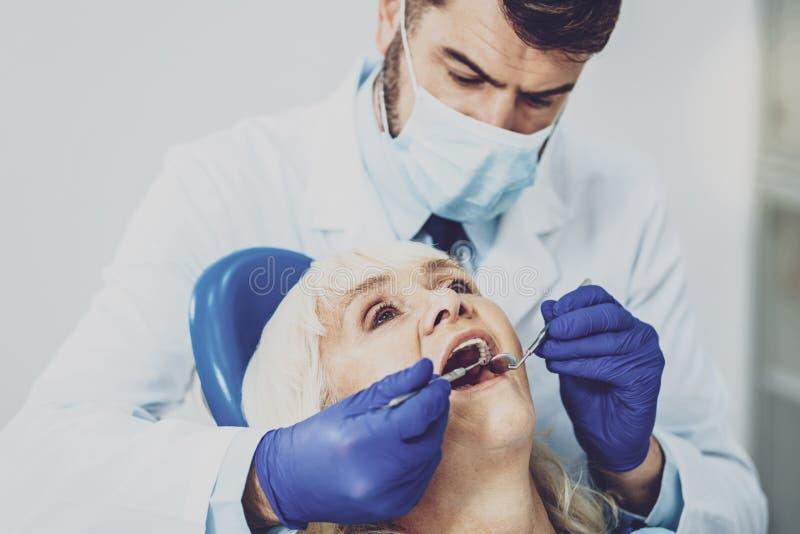 Ciérrese para arriba de stomatologist competente mientras que trabaja foto de archivo
