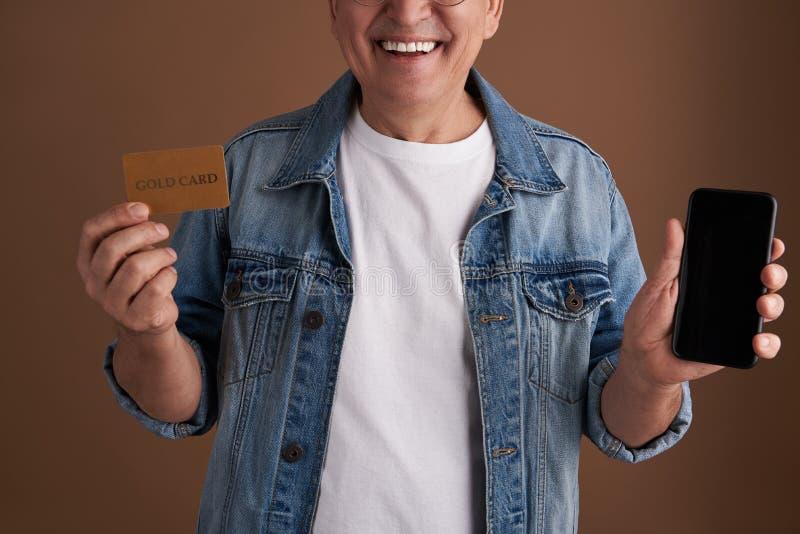 Ciérrese para arriba de tarjeta del oro y del artilugio moderno en manos del hombre sonriente fotografía de archivo