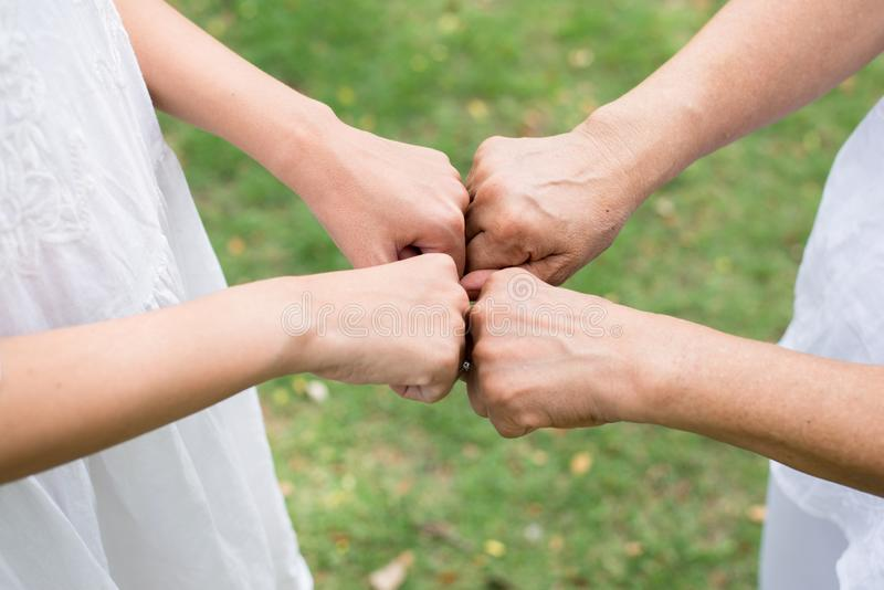Ci?rrese para arriba de topet?n de donante mayor del pu?o de la mujer asi?tica de la mano a las mujeres jovenes de las manos en a foto de archivo