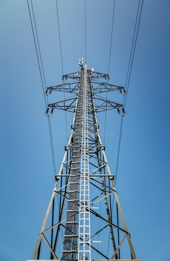 Ciérrese para arriba de torre eléctrica y del cielo azul Energía renovable y rejilla elegante fotos de archivo