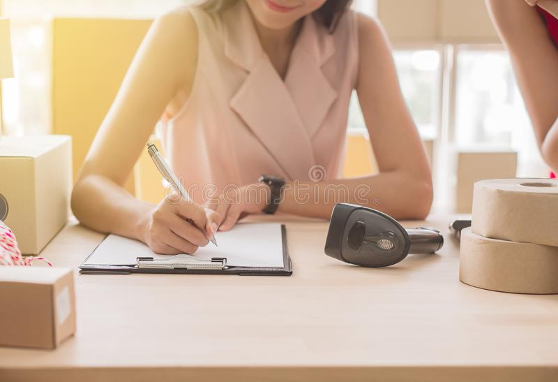 Ciérrese para arriba de trabajo del dueño de la mujer de la mano sobre el escritorio, la pequeña empresa, el negocio de la PME y  imagenes de archivo
