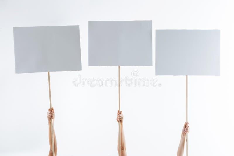 Ciérrese para arriba de tres muestras de la protesta foto de archivo