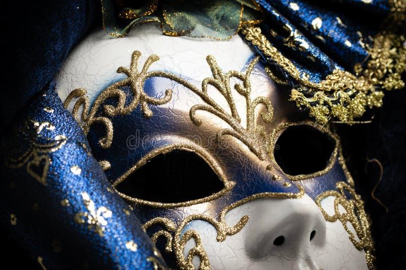 Ciérrese para arriba de un azul con la máscara veneciana tradicional elegante del oro sobre el fondo blanco fotografía de archivo libre de regalías
