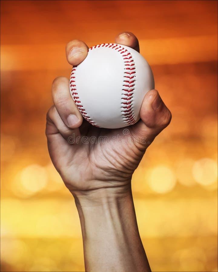 Ciérrese para arriba de un béisbol con una mano de la jarra imagenes de archivo