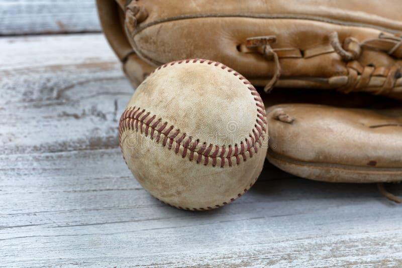 Ciérrese para arriba de un béisbol y de un mitón usados en el CCB de madera del vintage blanco fotografía de archivo