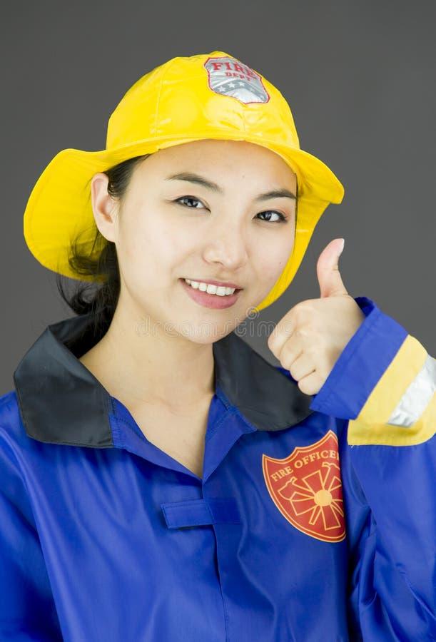 Ciérrese para arriba de un bombero de la señora que muestra los pulgares encima del gesto foto de archivo