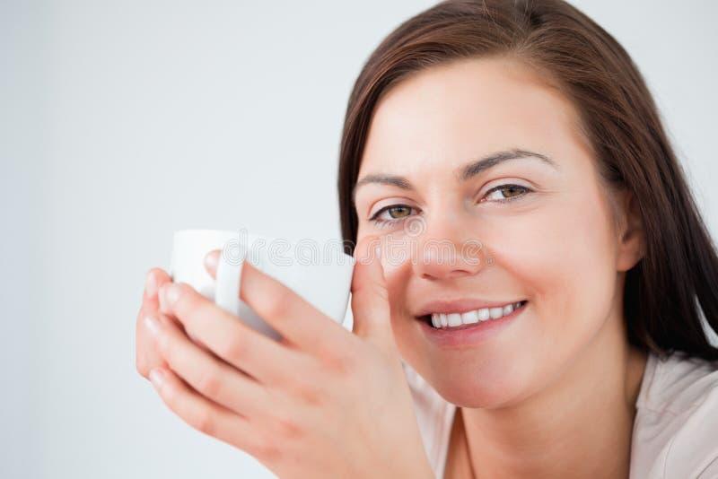 Ciérrese para arriba de un brunette hermoso que goza de un café imagen de archivo libre de regalías