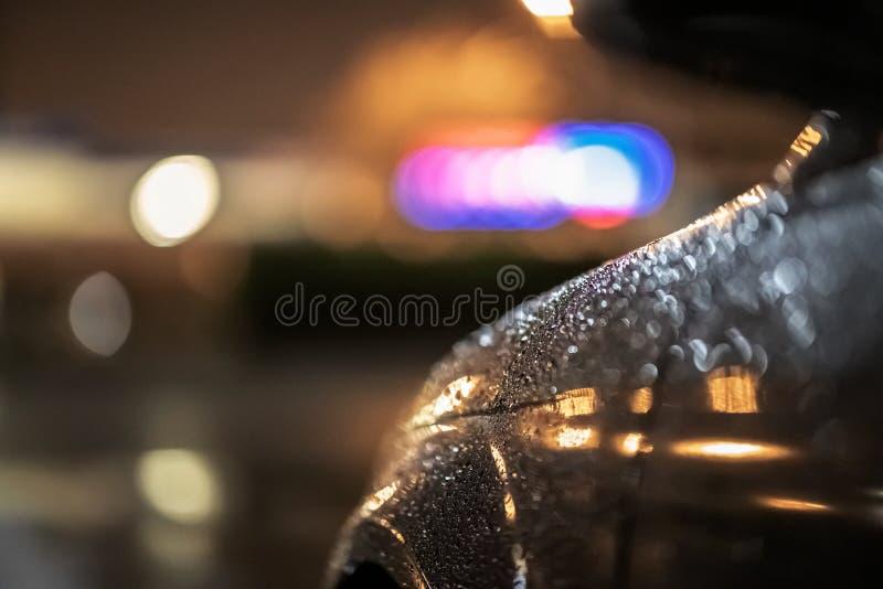 Ciérrese para arriba de un coche negro dramático en la noche, esperando en luces de calle en las fuertes lluvias fotos de archivo