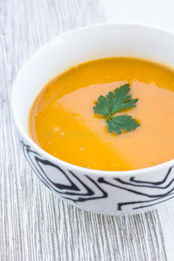 Ciérrese para arriba de un cuenco de sopa de la zanahoria, de la calabaza y de patata dulce foto de archivo