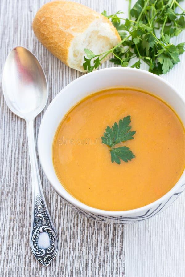 Ciérrese para arriba de un cuenco de sopa de la zanahoria, de la calabaza y de patata dulce imagenes de archivo