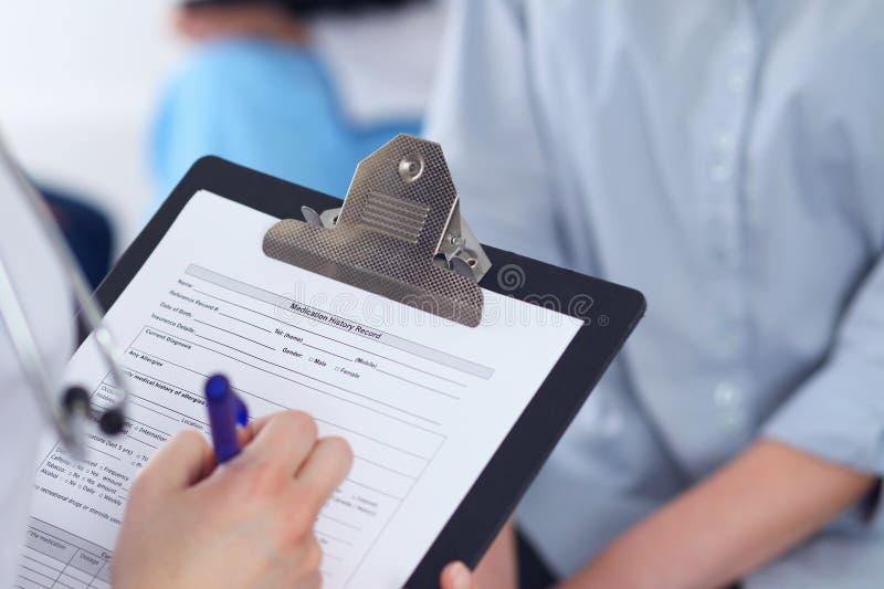 Ciérrese para arriba de un doctor de sexo femenino que completa el formulario de inscripción mientras que habla con el paciente C fotografía de archivo libre de regalías