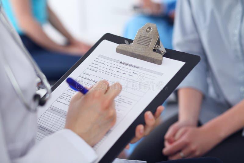 Ciérrese para arriba de un doctor de sexo femenino que completa el formulario de inscripción mientras que habla con el paciente C foto de archivo libre de regalías