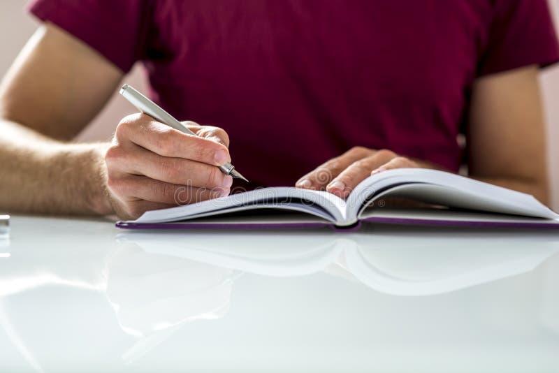 Ciérrese para arriba de un estudiante Writing Notes o de la preparación en un Noteb limpio imagenes de archivo