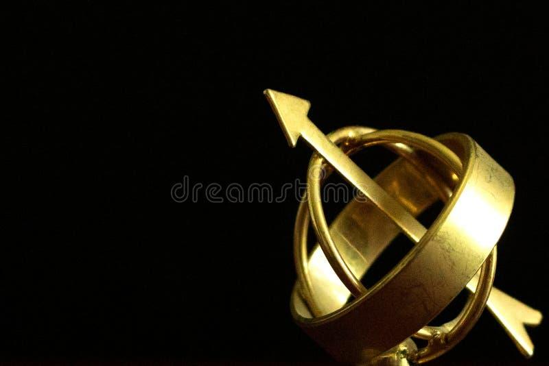 Ciérrese para arriba de un globo antiguo de oro hermoso del astrolabio en oscuridad imagenes de archivo