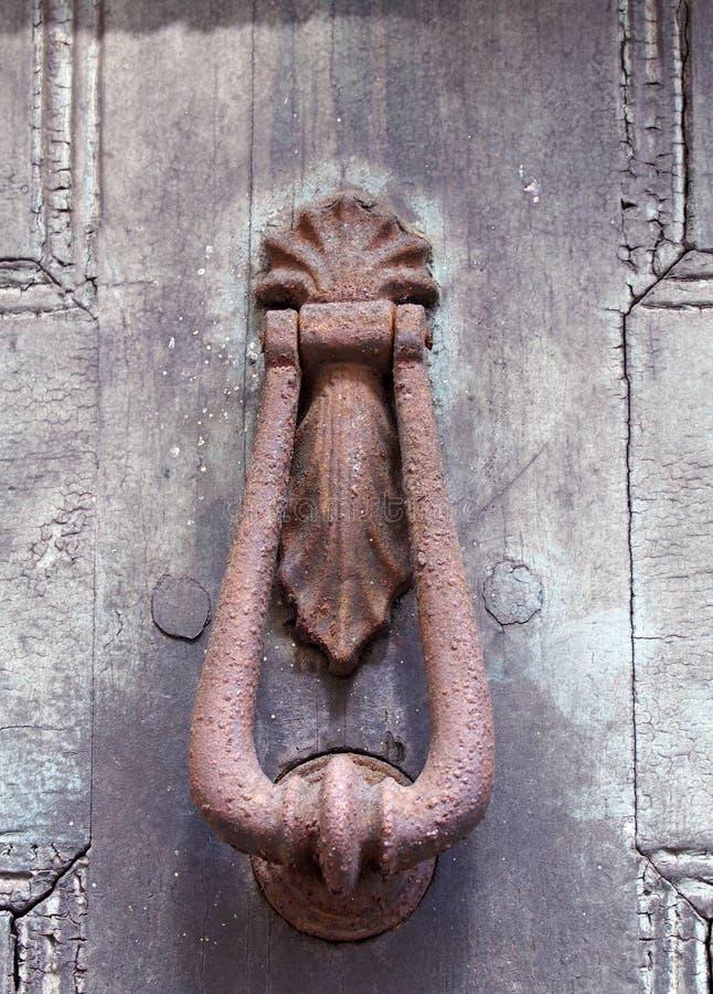 Ciérrese para arriba de un golpeador de puerta ornamental oxidado marrón viejo del hierro en una puerta pintada negra descolorada fotografía de archivo libre de regalías
