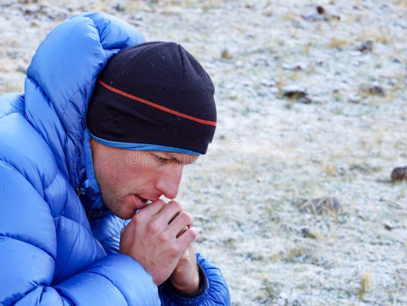 Ciérrese para arriba de un haber concentrado y el escalador de montaña pensativo en chaqueta gruesa del plumón perdió en pensamie fotografía de archivo libre de regalías