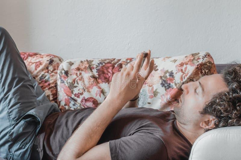 Ciérrese para arriba de un hombre caucásico relajado que usa el teléfono elegante que miente en el sofá en la sala de estar en ca fotos de archivo libres de regalías