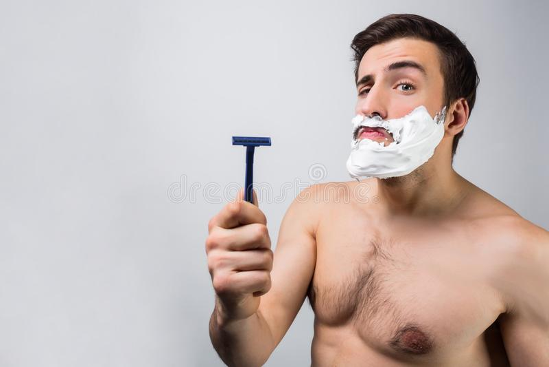 Ciérrese para arriba de un hombre con las tetas al aire que se coloca en el sitio blanco y que señala en su maquinilla de afeitar fotografía de archivo libre de regalías
