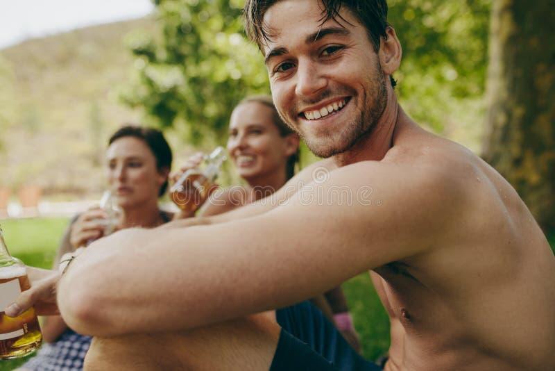 Ciérrese para arriba de un hombre el día de fiesta que se sienta con dos amigos femeninos imagenes de archivo