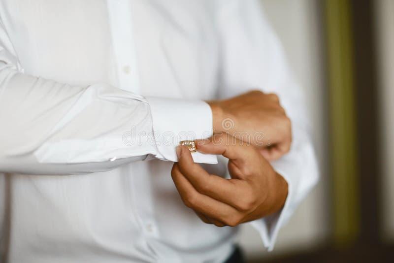 Ciérrese para arriba de un hombre de la mano cómo lleva la camisa y la mancuerna blancas, con las piedras, boda lujosa foto de archivo