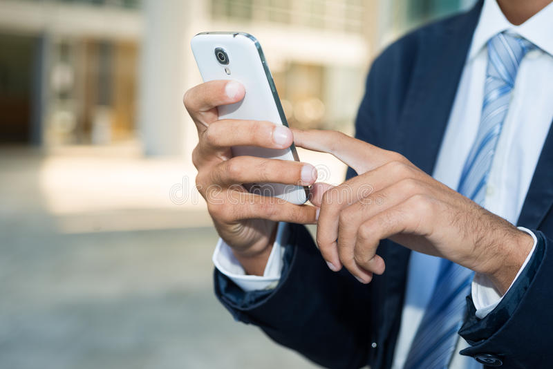 Ciérrese para arriba de un hombre que usa su smartphone foto de archivo libre de regalías