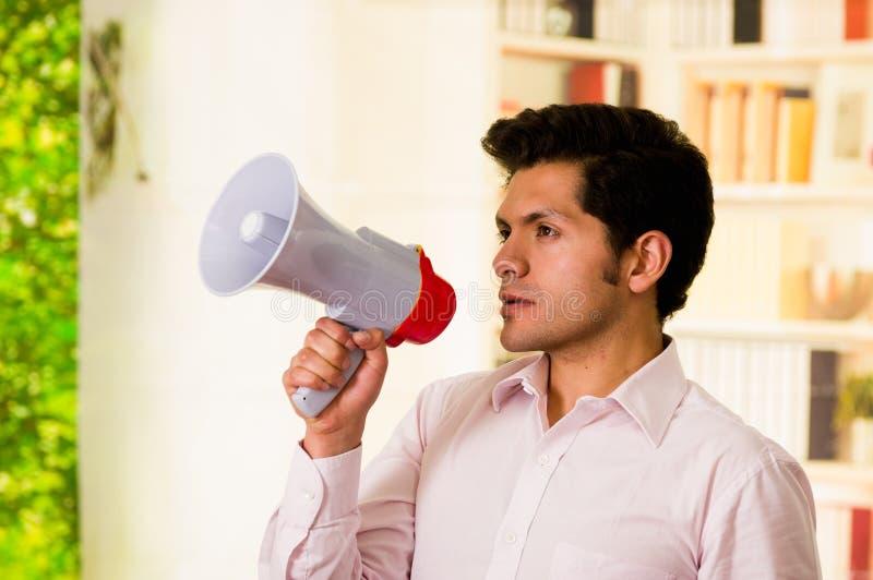 Ciérrese para arriba de un hombre serio hermoso que sostiene un megáfono en su mano en un fondo borroso imágenes de archivo libres de regalías