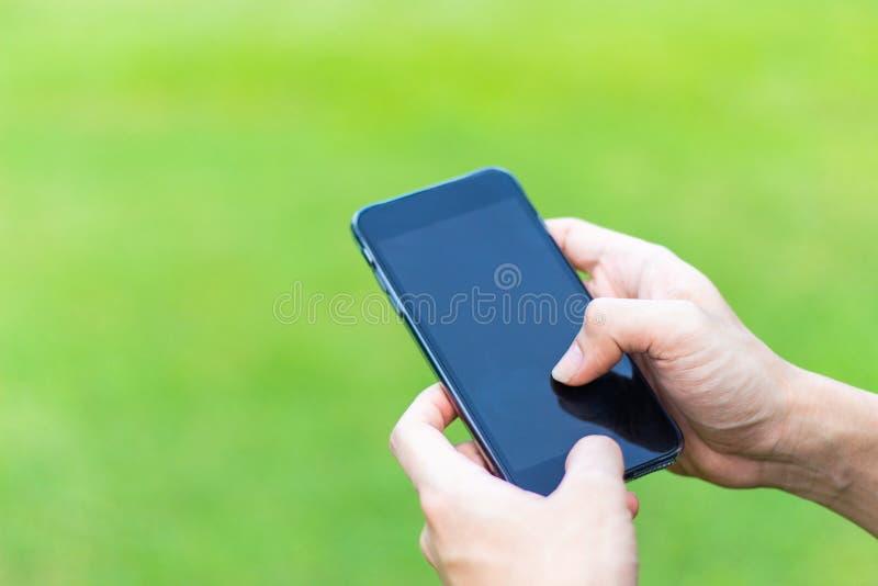 Ciérrese para arriba de un hombre usando el teléfono elegante móvil en el parque manos a fotos de archivo libres de regalías