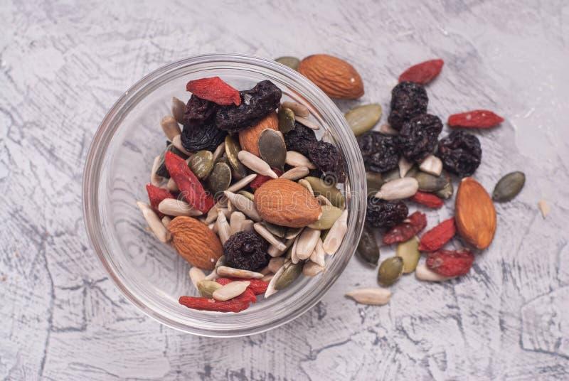 Ciérrese para arriba de un mezclado de las nueces, frutas secas en bol de vidrio en Gray Textured Background Visión superior imágenes de archivo libres de regalías