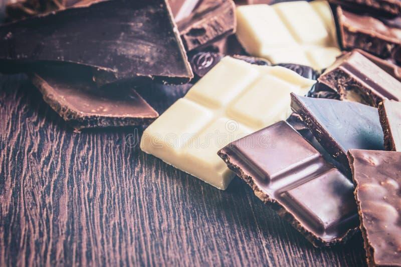 Ciérrese para arriba de un montón de los diversos pedazos del chocolate sobre fondo de madera oscuro Oscuridad, leche, blanco y b foto de archivo libre de regalías