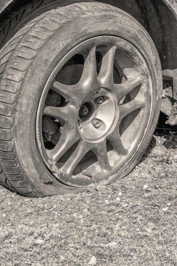 Ciérrese para arriba de un neumático desinflado en el coche fotos de archivo