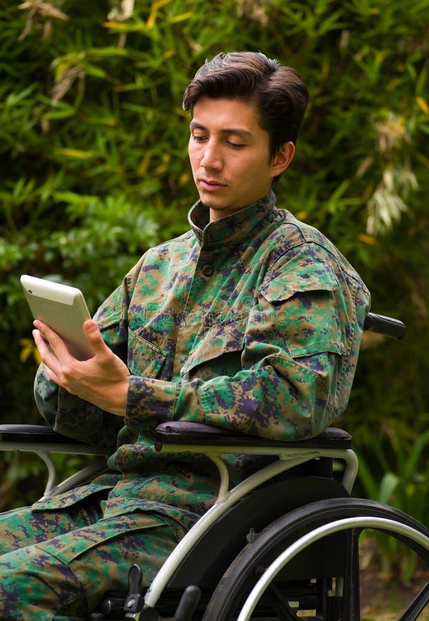 Ciérrese para arriba de un soldado hermoso que se sienta en la silla de rueda usando su tableta con ambas entregas, y del uniform fotografía de archivo libre de regalías