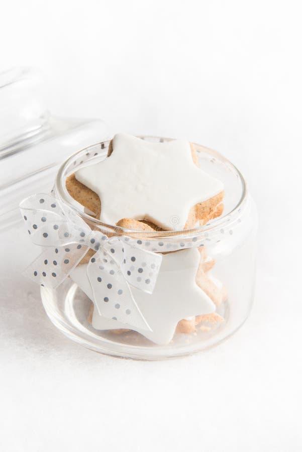 Ciérrese para arriba de un tarro de cristal por completo con las galletas hechas en casa de la estrella de la Navidad sobre el fo foto de archivo libre de regalías