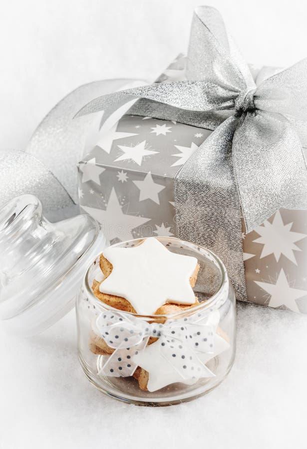 Ciérrese para arriba de un tarro de cristal por completo con las galletas hechas en casa de la estrella de la Navidad sobre el fo fotos de archivo