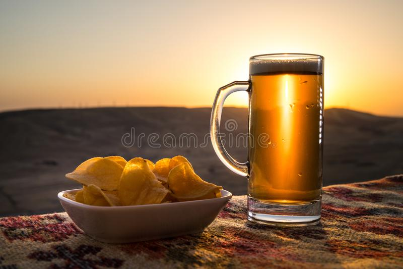 Ciérrese para arriba de un vidrio de cerveza con los bocados en el fondo de la luz del sol, cerveza en hierba foto de archivo libre de regalías