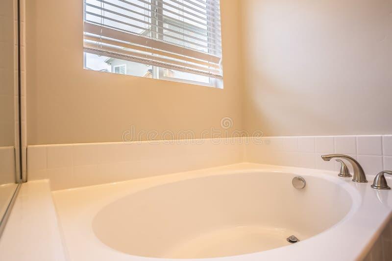 Ciérrese para arriba de una bañera oval blanca con el grifo de acero inoxidable dentro de un cuarto de baño foto de archivo libre de regalías