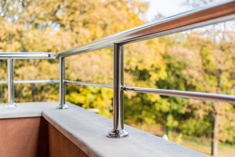 Ciérrese para arriba de una barandilla del metal del balcón Opinión del otoño en el fondo imágenes de archivo libres de regalías