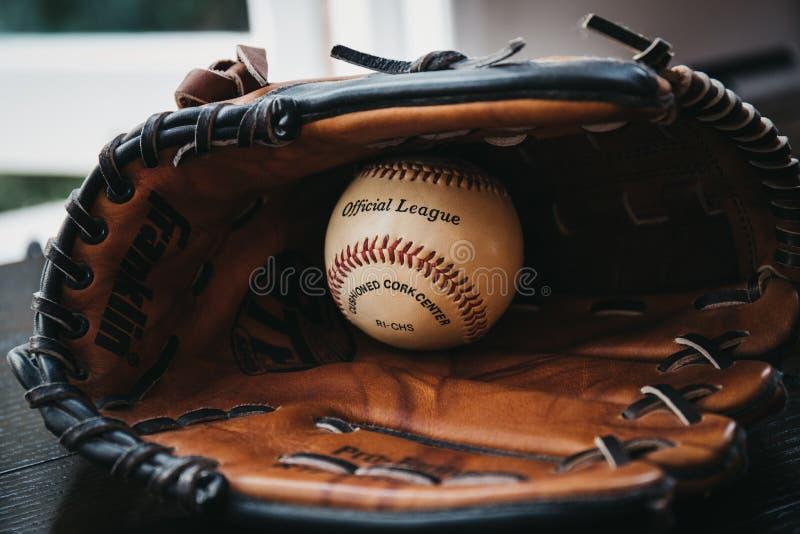 Ciérrese para arriba de una bola blanca del béisbol dentro del guante de béisbol del moreno imagen de archivo