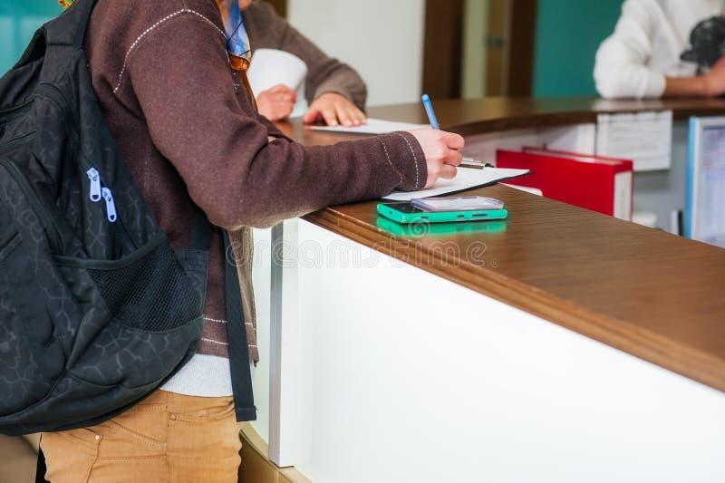 Ciérrese para arriba de una escritura de la mano de la mujer o de la firma en un documento en una zona de la recepción de la clín fotos de archivo